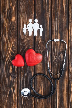 top view of white figures of family holding hands, red hearts symbols and stethoscope