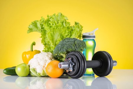 close-up view of dumbbell, bottle of water and fresh fruits and vegetables on yellow