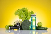 close-up view of fresh green apples and vegetables, dumbbells and bottle of water on yellow