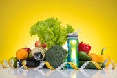 close-up view of fresh fruits and vegetables, measuring tape, bottle of water and dumbbells on yellow