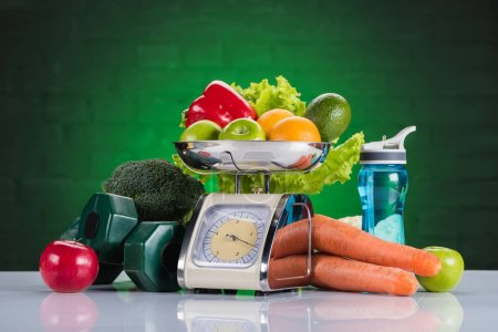Photo for Close-up view of fresh fruits and vegetables on scales, dumbbells and bottle of water on green - Royalty Free Image