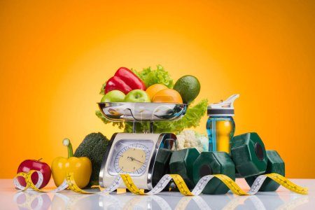 Fresh fruits and vegetables on scales, sports bottle with water, dumbbells and measuring tape on yellow