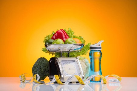 fresh fruits and vegetables on scales, sports bottle with water and measuring tape on yellow