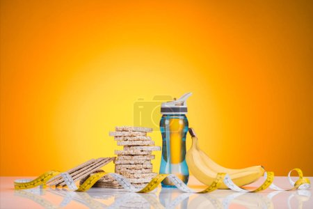 close-up view of sports bottle with water, diet cookies, measuring tape and banana on yellow