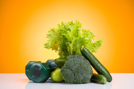 close-up view of green dumbbells and fresh fruits and vegetables on yellow