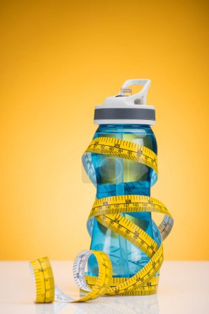 Photo for Close-up view of sports bottle with water and measuring tape on yellow - Royalty Free Image