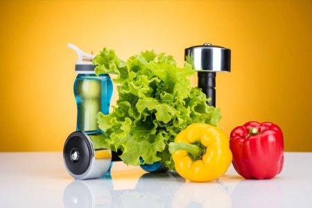 Foto de Vista cercana de pesas, verduras frescas y botella de agua en amarillo - Imagen libre de derechos