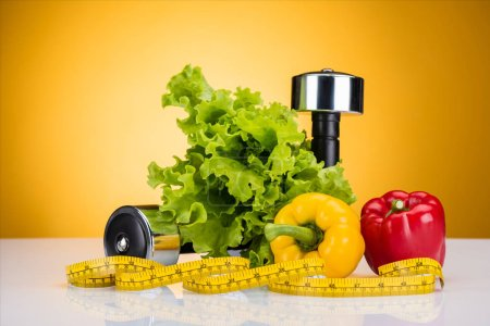 close-up view of fresh vegetables, measuring tape and dumbbells on yellow