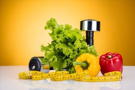 Photo pour Vue rapprochée des légumes frais, ruban à mesurer et haltères sur jaune - image libre de droit