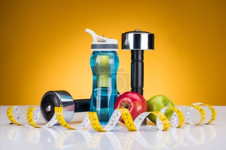 Photo for Close-up view of dumbbells, measuring tape, bottle of water and apples on yellow - Royalty Free Image