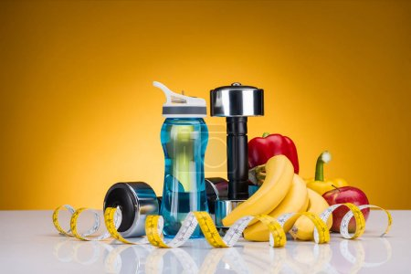 Photo for Close-up view of dumbbells, bottle of water, measuring tape and peppers with fruits on yellow - Royalty Free Image