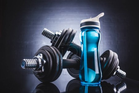 Photo for Close-up view of sports bottle full of water and dumbbells, sport and healthy lifestyle concept - Royalty Free Image
