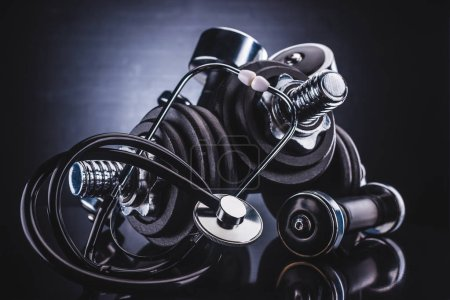 close-up view of various dumbbells and stethoscope, healthy lifestyle concept
