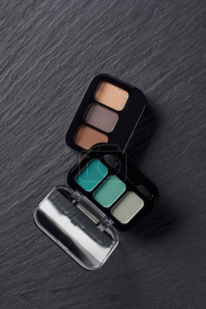Set of eye shadows palettes on dark slate background