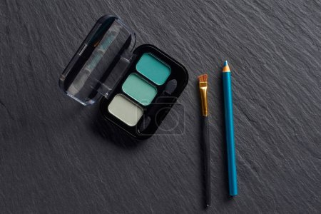Eye shadows in blue tones with pencil and brush on dark slate background