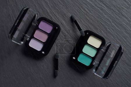 Set of eye shadows palettes with applicators on dark slate background