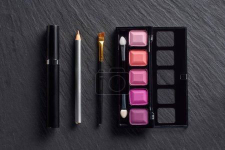 Makeup set with eye shadows, pencil and mascara on dark slate background
