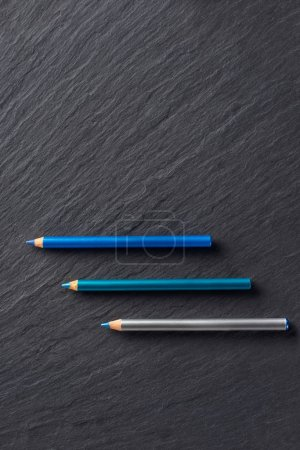 Makeup pencils in blue tones on dark slate background