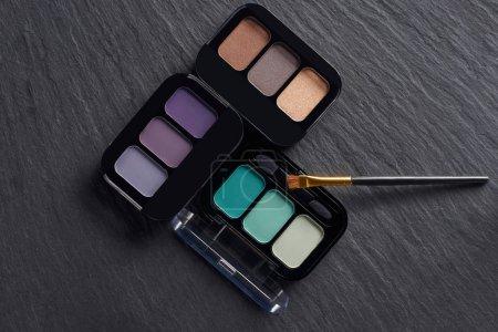 Eye shadow palettes with brush on dark slate background