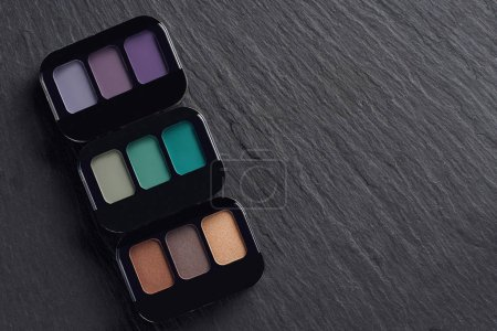 Makeup palettes in a row on dark slate background