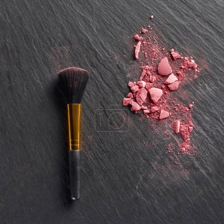 Pink blush pieces and brush on dark slate background