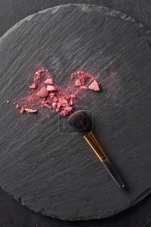 Broken blush and black brush on round slate background