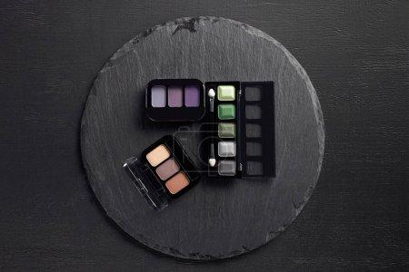 Set of eye shadows palettes on round slate background
