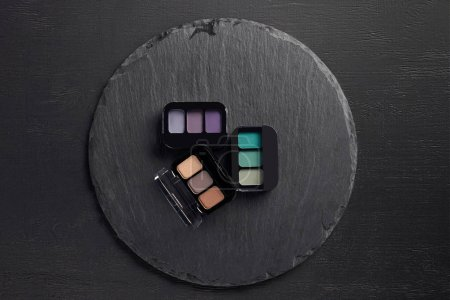 Eye shadows palettes on round slate background