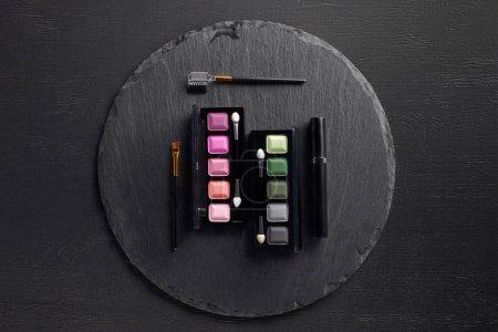 Photo pour Ensemble de palettes d'ombres à paupières avec brosses sur fond d'ardoise ronde - image libre de droit