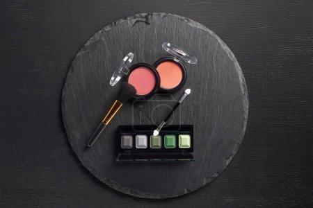 Photo pour Set de maquillage avec pinceau, fard à joues et ombres à paupières sur fond d'ardoise ronde - image libre de droit