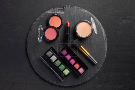 Makeup set with eye shadows and lipstick on round slate background