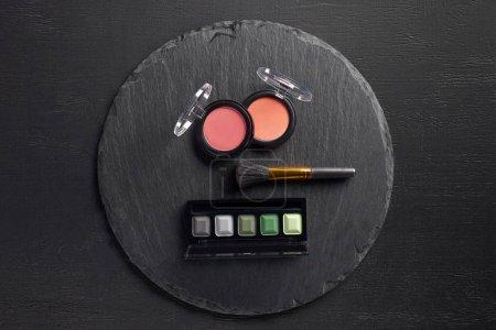 Blush and eye shadows with brush on round slate background