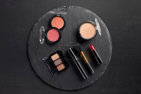 Makeup set with eye shadows and blush on round slate background
