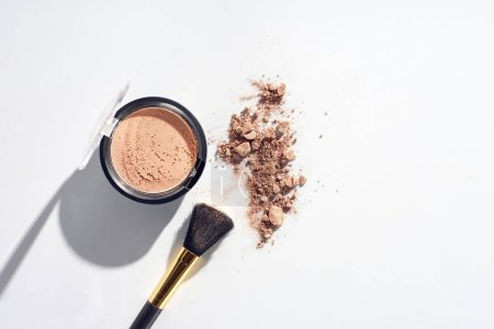 Face powder with brush on white background