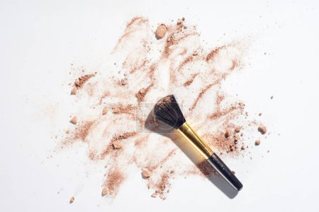 Scattered powder foundation with brush on white background