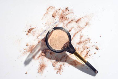 Pressed powder and makeup brush on white background with scattered foundation