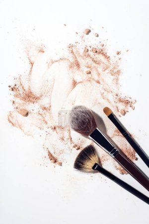 Foundation smears and makeup brushes on white background