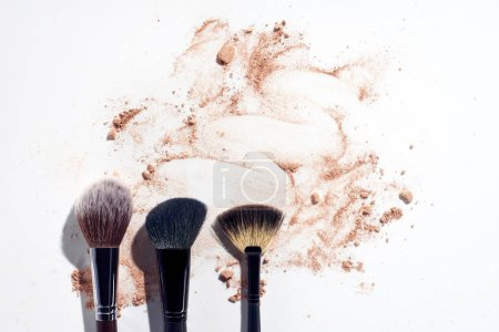 Three face brushes on white background with scattered face powder