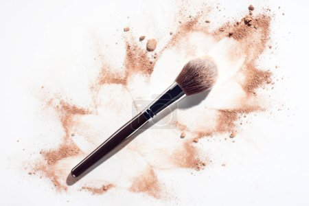 Plush makeup brush on white background with scattered face powder