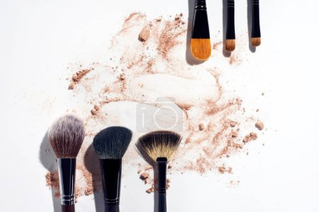 Frame of makeup brushes with powder foundation on white background