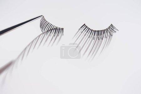 Applying fake eyelashes on white background