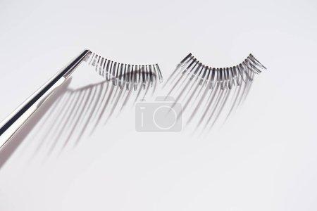 Fixing fake eyelashes with tweezers on white background