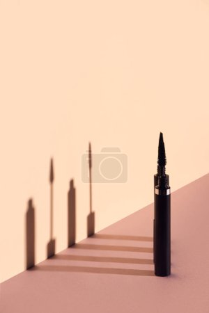 Set of mascara tubes with brushes on beige background