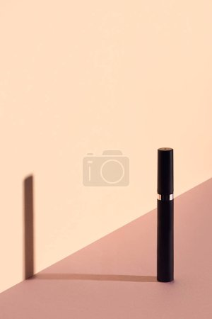 Single mascara tube on beige background
