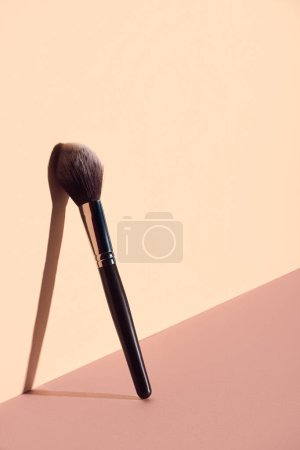 Plush makeup brush on beige background