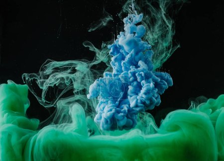 close-up view of abstract green and blue flowing paint on black background