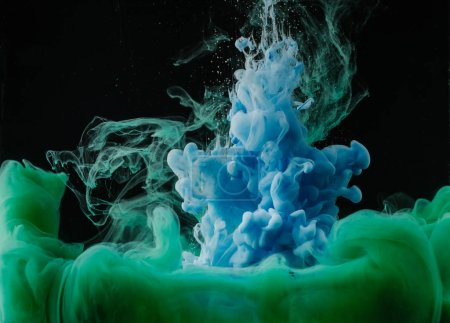 Photo for Close-up view of abstract green and blue flowing ink on black background - Royalty Free Image