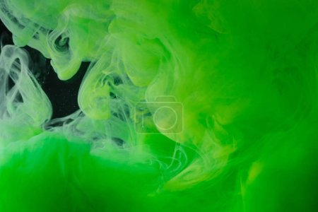 close-up view of bright green abstract flowing ink on black background