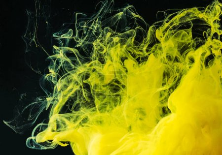 close-up view of bright yellow flowing paint on black background