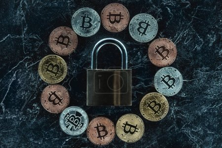 top view of arranged lock and various bitcoins on dark marble surface